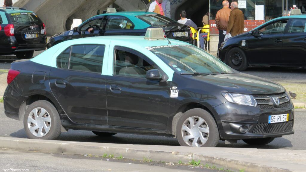Typical Portuguese taxi in black and green color; After arriving to lisbon by car