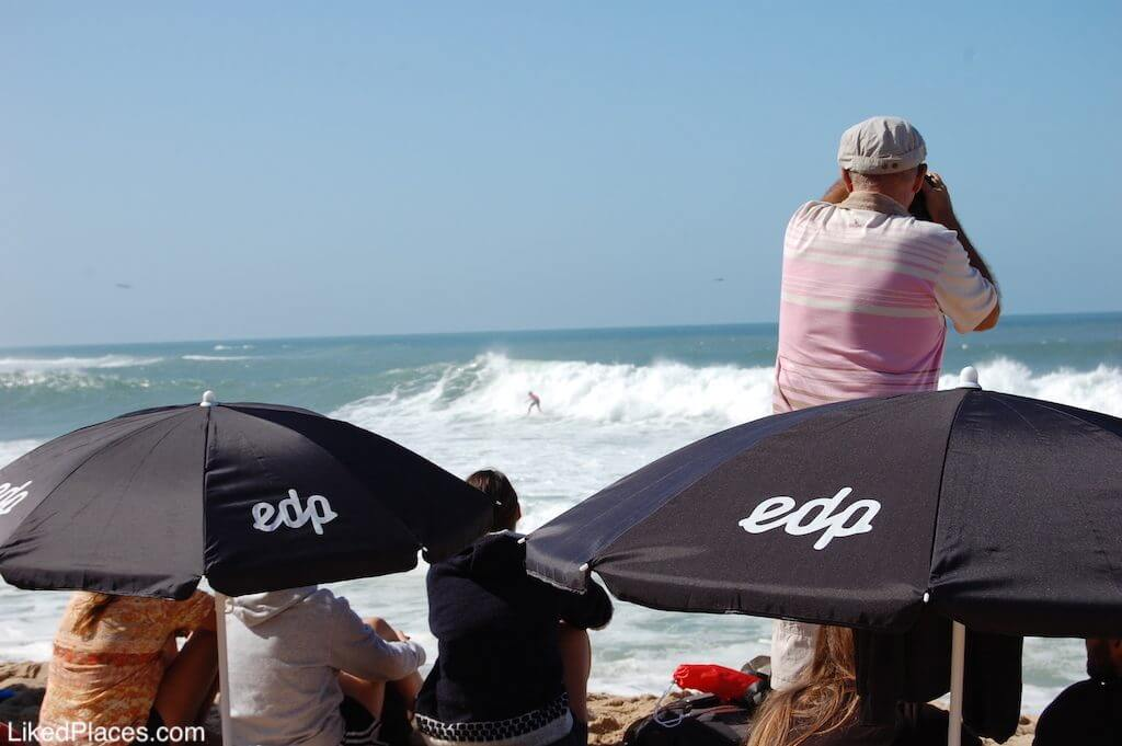 People sitting on the sand watching and photographing the Billabong Pro Ericeira, in Ribeiradilhas beach. In the background surfer surfing wave.