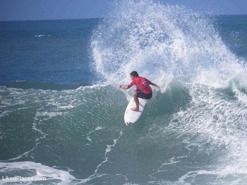 Surfista de tshirt vermelha a surfar uma onda numa prancha branca, na Praia de Ribeiradilhas no Billabong Pro Ericeira
