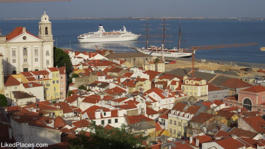View of Alfama and boats on the Tagus River. Invest in Portugal in real estate