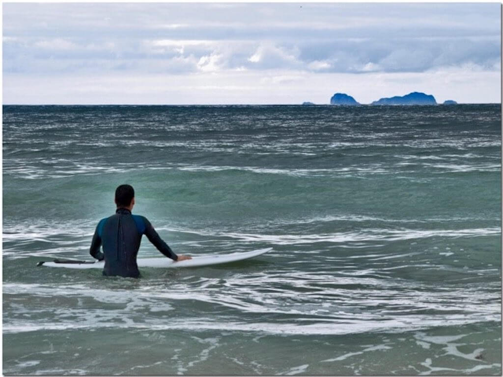 Surfer grabbing board in water at Baleal Beach with Berlengas Islands in the background, Peniche